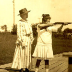 Annie Oakley watches as young girl takes aim