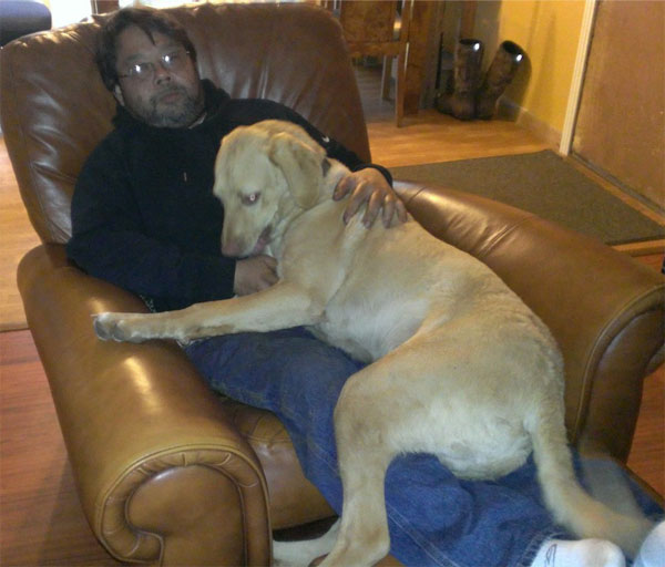 Charlie is sitting on Tim's lap in the recliner. Charlie is so big you can hardly see any of Tim's body--just his head above Charlie's head.