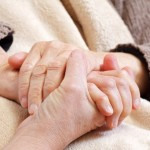 Younger person holding elderly person's hand.